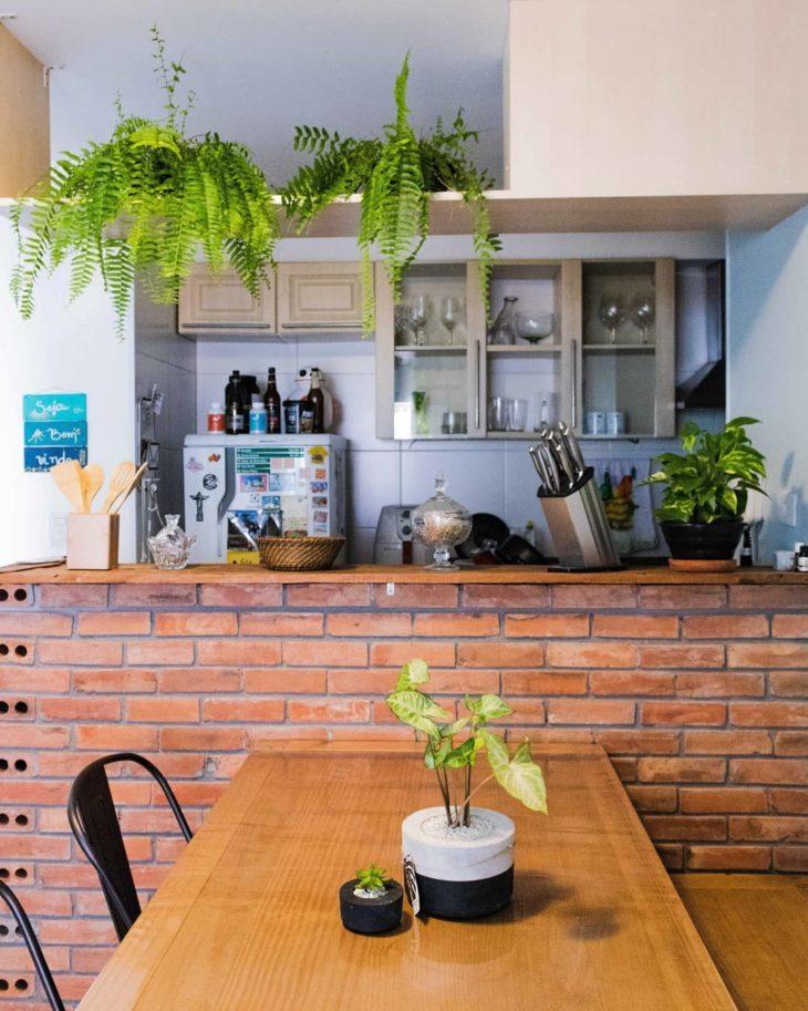 Cozinha aberta com parede de tijolinho aparente com samambaias.