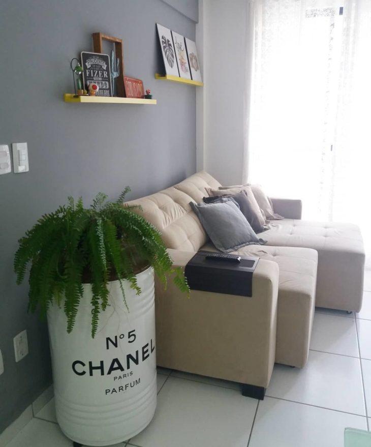 Sala simples decorada com samambaia e tonel da channel.