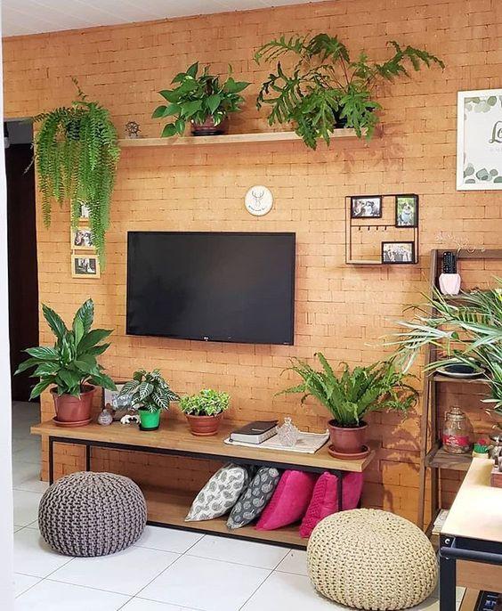 Sala simples com parede de tijolinho aparente decorada com plantas.