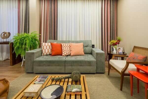 Sala moderna com sofá cinza e samambaia.