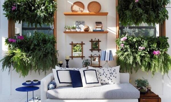 Área externa decorada com samambaias e sofá branco.