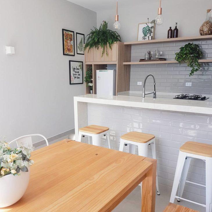 Cozinha americana moderna com quadros e azulejo de tijolinho cinza.