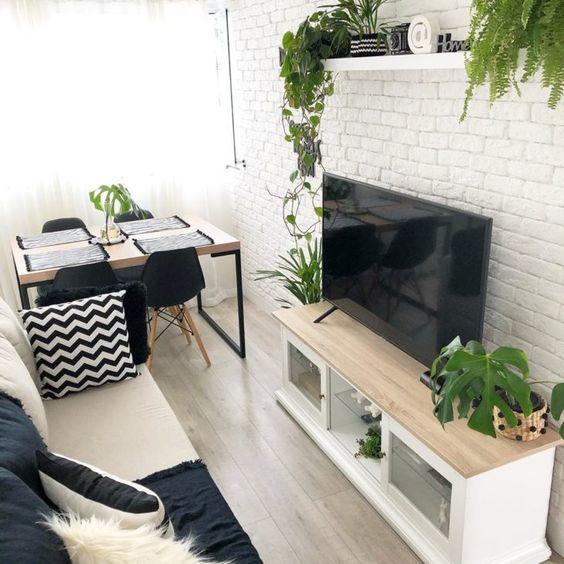 Sala pequena simples com parede de tijolinho branco e decoração preta e branca.