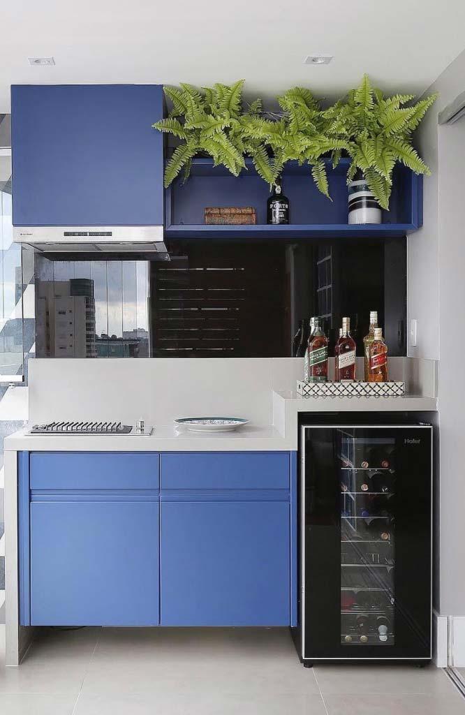 Varanda gourmet moderna com armários azuis.