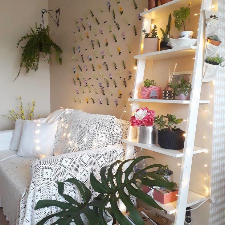 Sala pequena e simples decorada com plantas e parede de flores.