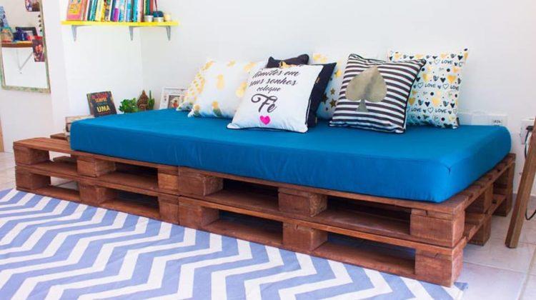 Sofá de pallet escuro com almofadas coloirdas.