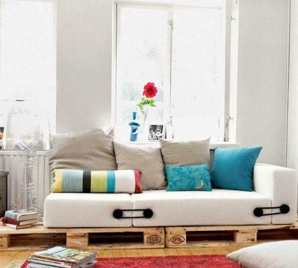 Sofá de pallet com almofada branca moderna.