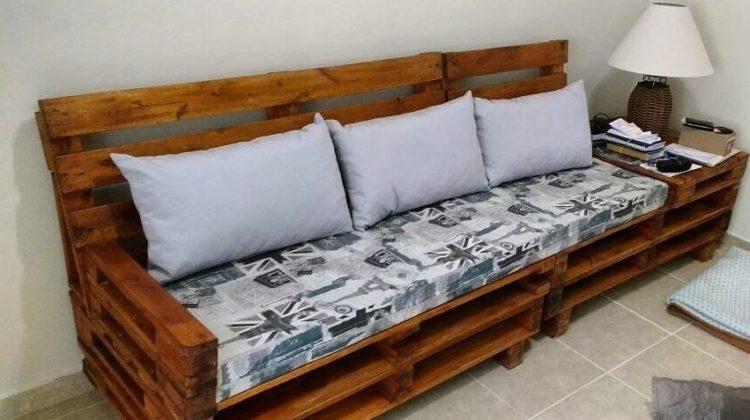 Sofá de pallet com encosto de madeira e almofadas.