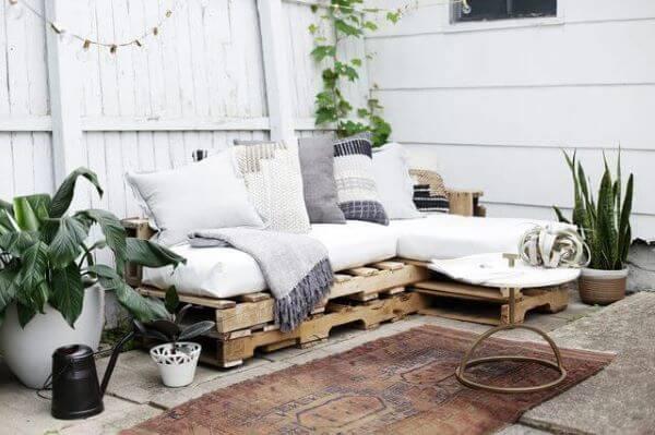 Varanda decorada com vasos de plantas e sofá de pallet.