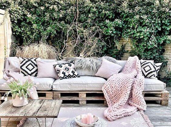 Varanda decorada com piso de madeira e sofá de pallet.