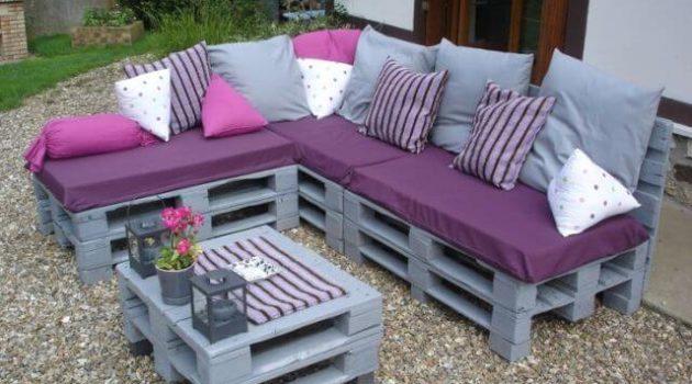 Sofá de pallet cinza com estofado roxo.