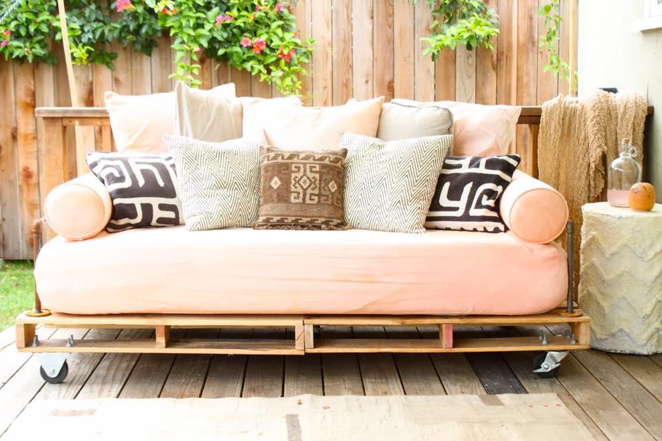 Sofá de pallet pequeno com almofada rosa.