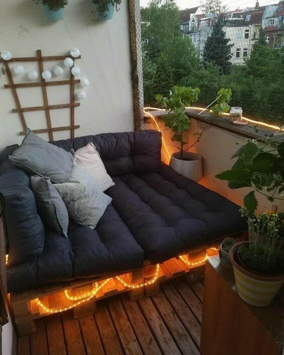 Varanda decorada com plantas e sofá.