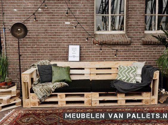 Sofá de pallet com encosto e almofada preta.