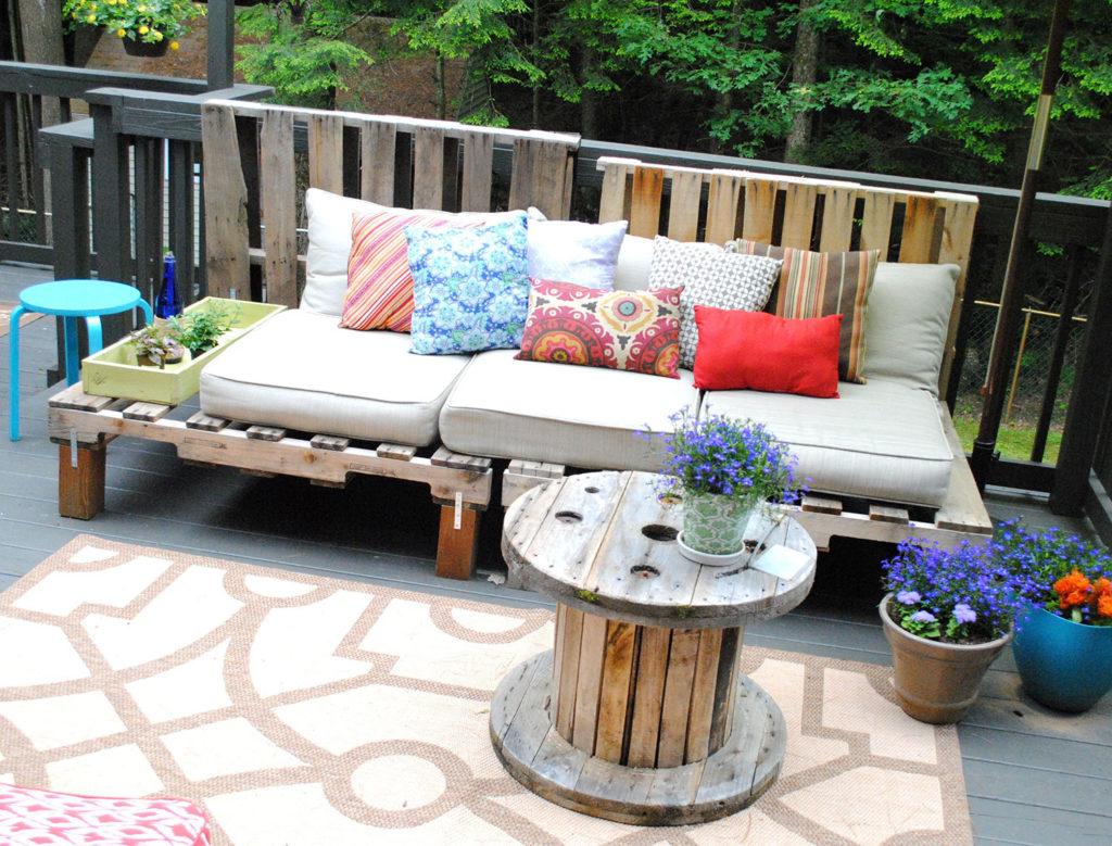 Varanda com sofá de pallet e vasos de plantas.