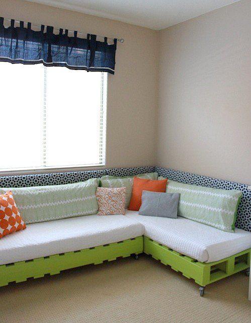 Sofá de pallet verde com almofadas decoradas.