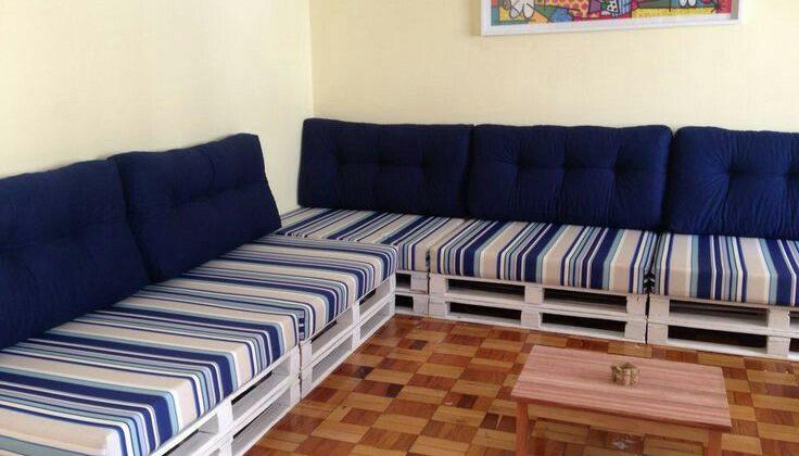 Sofá de pallet branca com almofadas azuis.