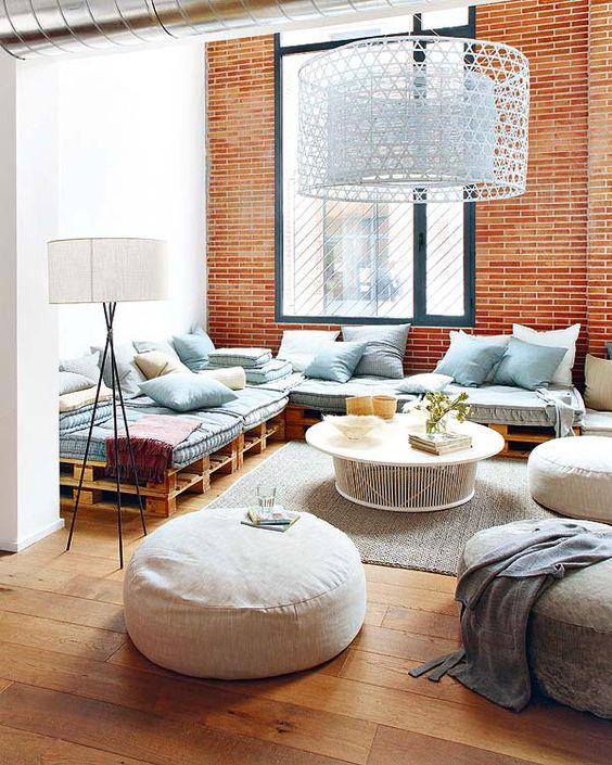 Sala de estar moderna com parede de plaqueta terracota e lustre gigante.