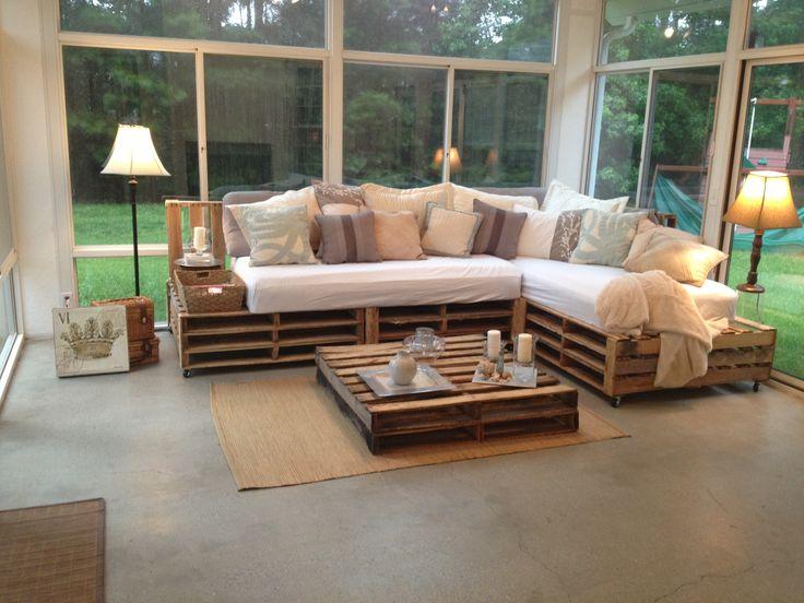 Sofá de pallet com estofado branco e mesa de centro.
