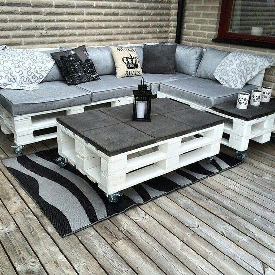 Sofá de pallet branco com estofado cinza e almofadas decoradas.