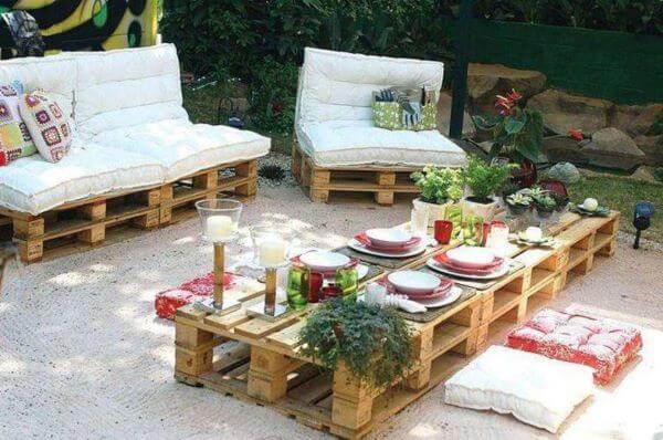 Jardim decorado com almofadas estofadas e mesa de centro.
