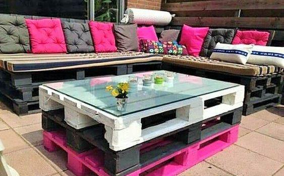 Sofá de pallet preto e mesa de centro colorida.