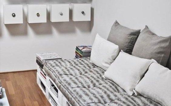 Sofá de pallet branco com livros e almofadas cinzas.