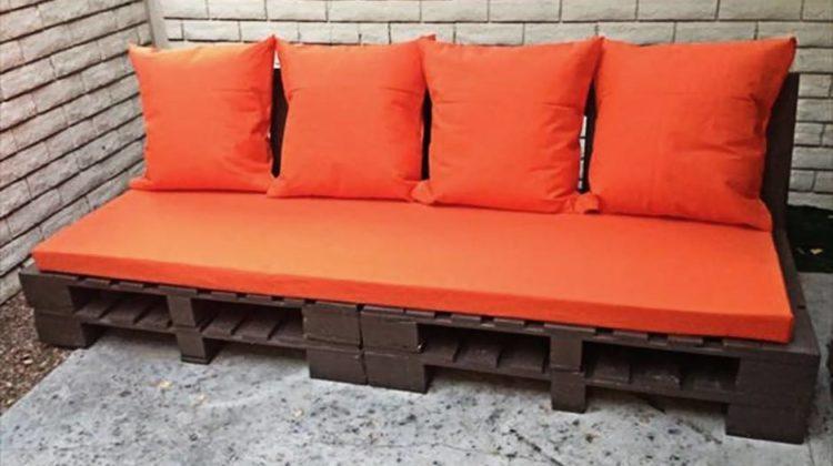 Sofá de pallet com madeira escura e almofada laranja.