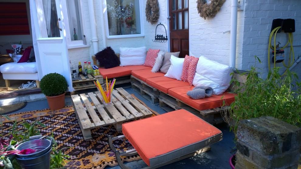 Varanda decorada com sofá de pallet e almofada laranja.