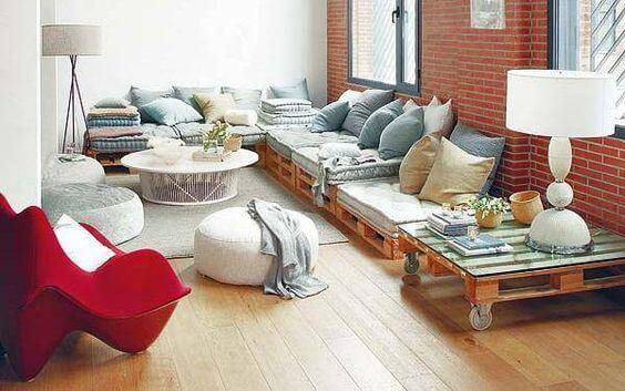 Sala de estar moderna com almofadas cinzas, parede de tijolinho e poltrona vermelha.