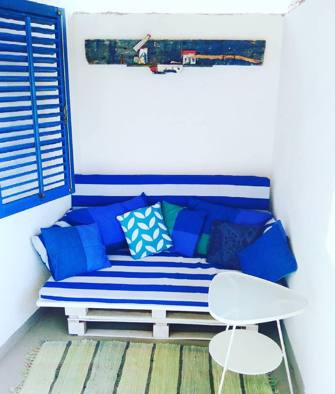 Sofá de pallet branco com almofadas azuis.