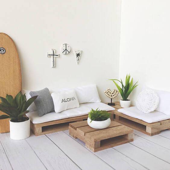 Sala de estar com decoração simples e branca com vasos de plantas.