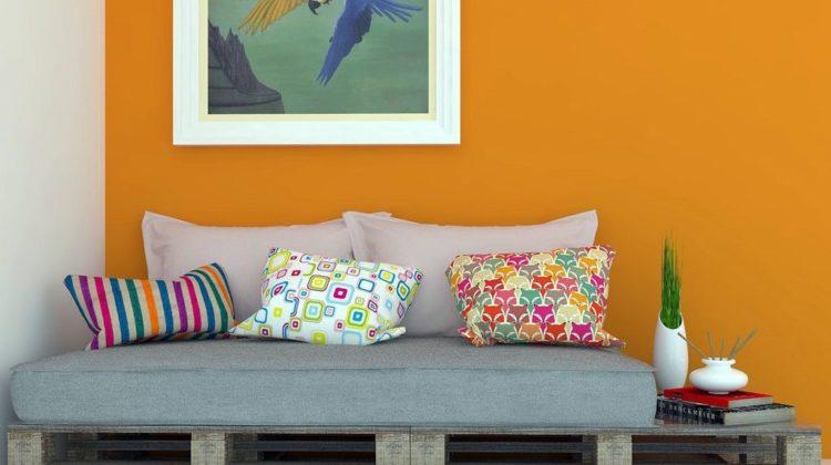 Sala com sofá de pallet e parede laranja.