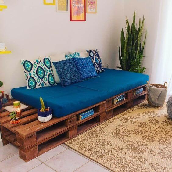 Sofá de pallet simples com almofadas azuis.