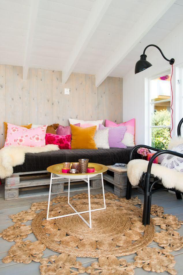 Sala moderna com almofadas coloridas, abajur de parede e cadeira preta.