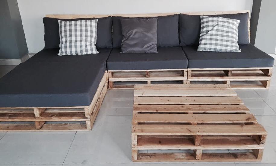 Sofá de pallet com estofado preto e mesa de centro.