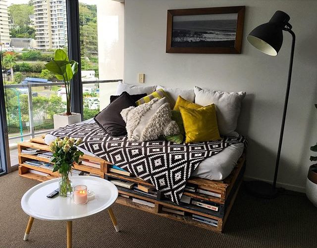 Varanda decorada com sofá de pallet com livros.