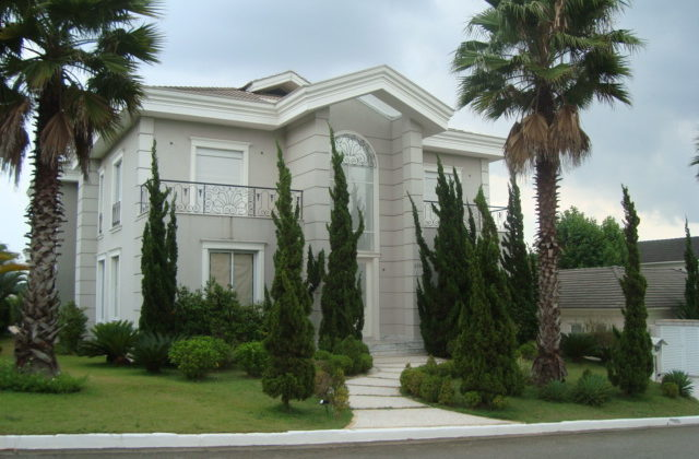 Mansão com área externa decorada com palmeira real e pinheiros.