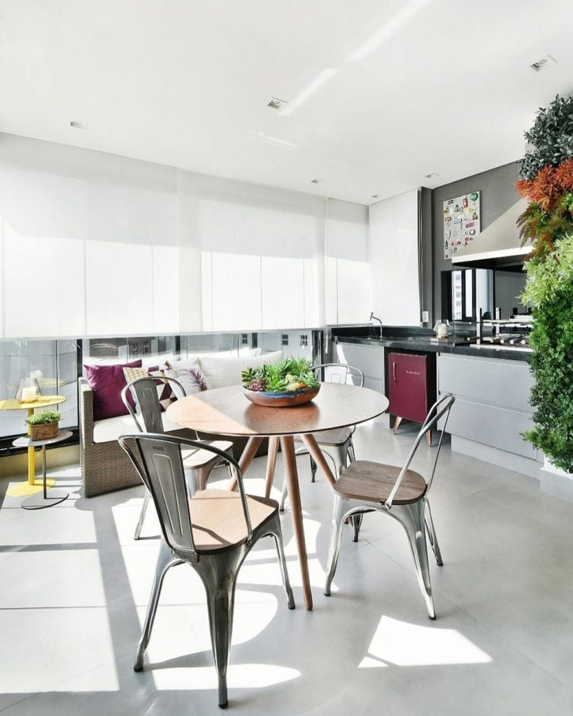 Cozinha externa com sofá de vime e mesa de madeira.