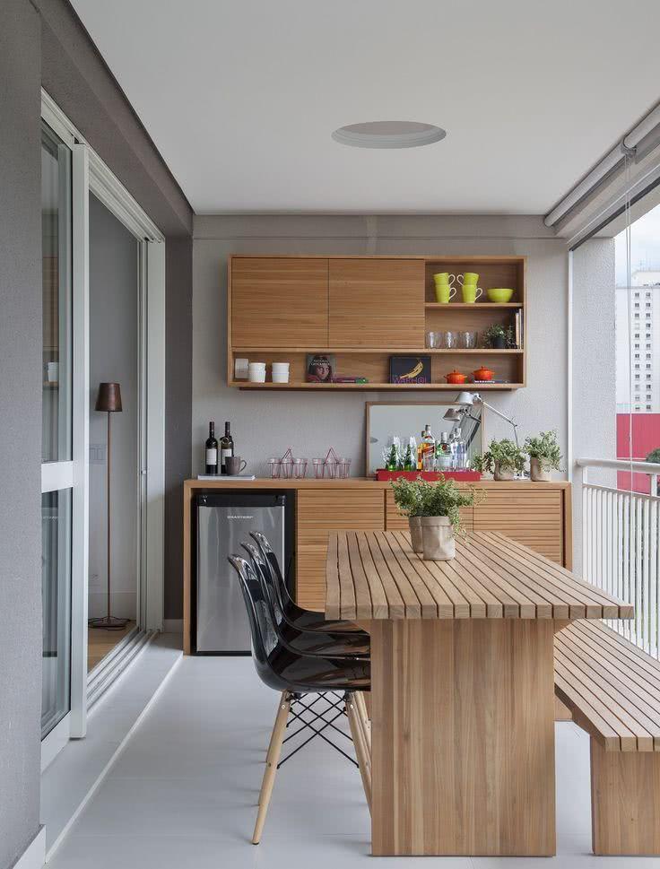 Varanda gourmet com mesa de madeira e armário planejado.