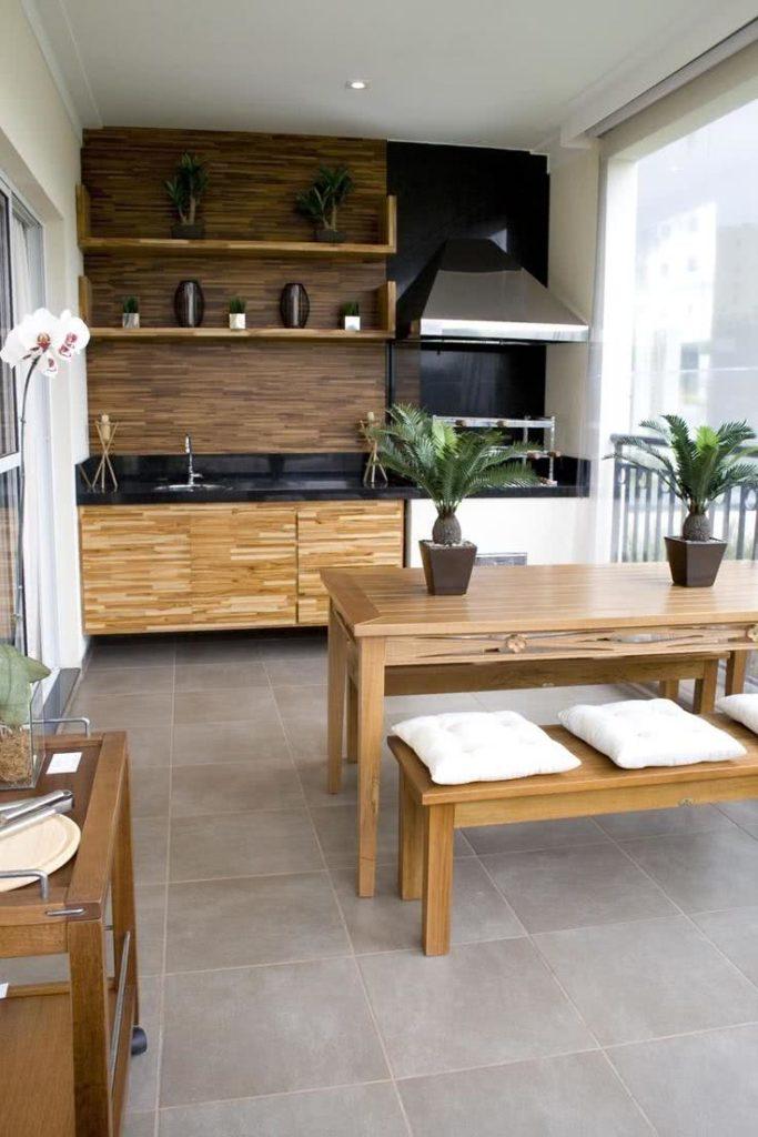 Varanda gourmet com mesa rústica de madeira.