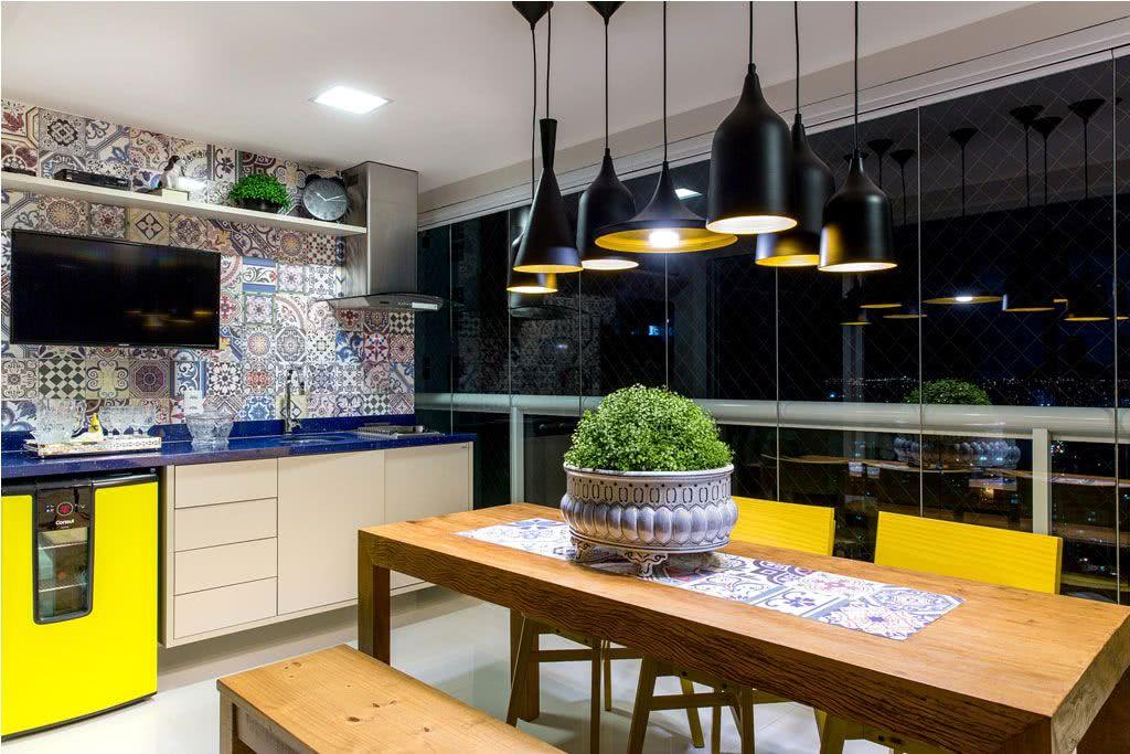 Varanda gourmet com mesa rústica e azulejo decorado.