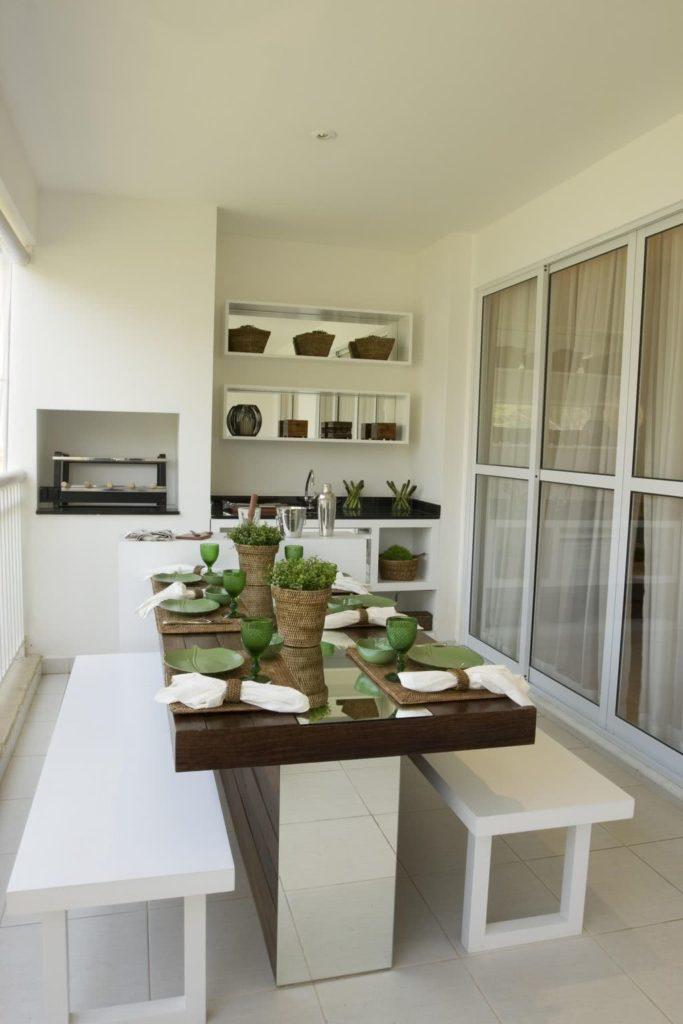 Varanda gourmet com mesa espelhada e decoração branca.