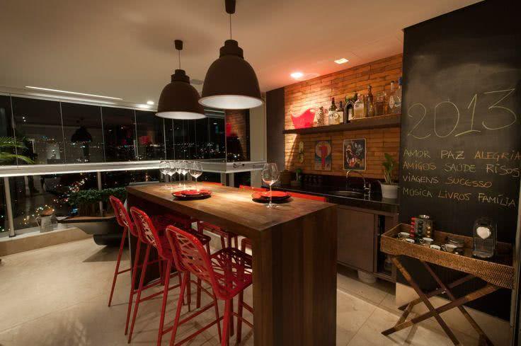 Varanda gourmet com decoração rústica e parede com tinta de lousa.