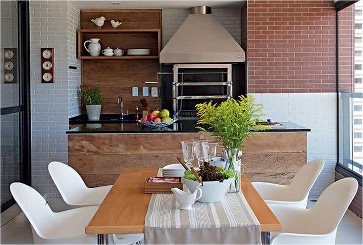 Varanda gourmet com mesa de madeira e plaquetas de terracota.
