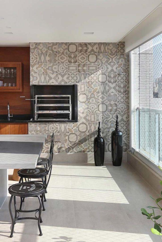 Varanda gourmet com azulejo decorado e churrasqueira elétrica.