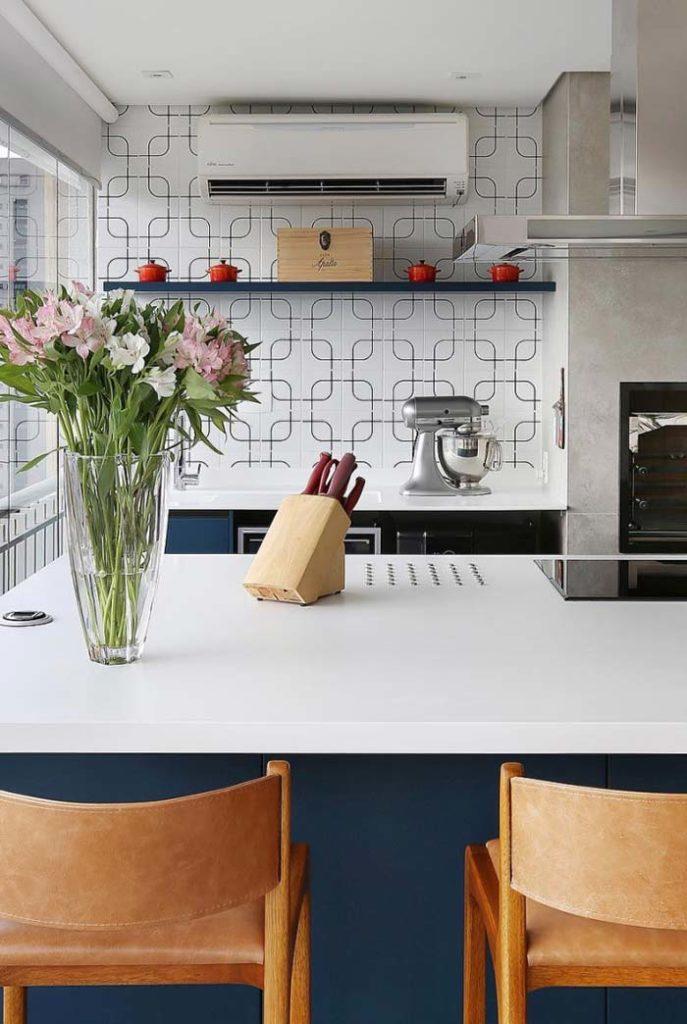 Varanda gourmet com azulejo moderno e bancada de madeira.