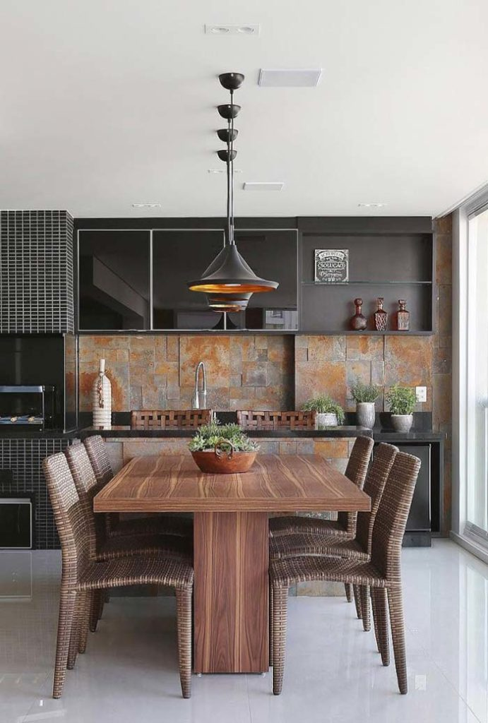 Varanda gourmet com azulejo de pedra e mesa de madeira.