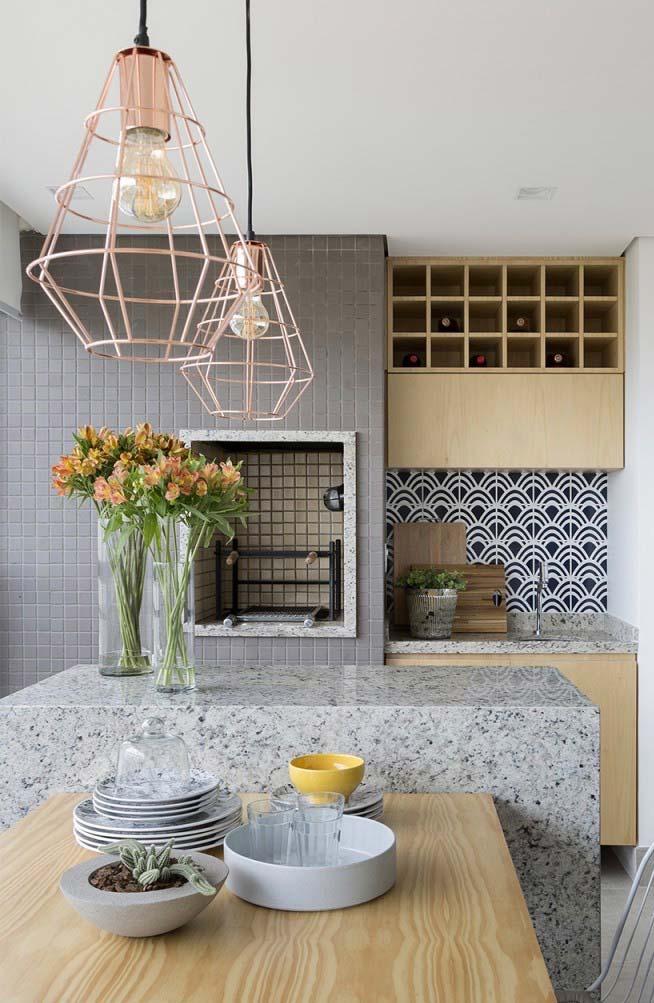 Varanda gourmet com azulejo hidráulico e bancada de granito.