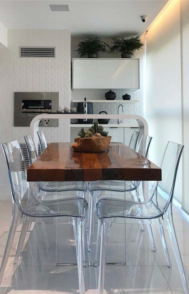Varanda gourmet com mesa moderna e cadeiras de acrílico.